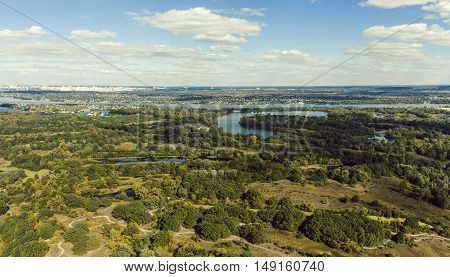 Panoramic view of the Kiev suburb from above. Aerial view. Outdoor. Beautiful photos of nature with fields river and reservoirs with high-rise buildings in the background.