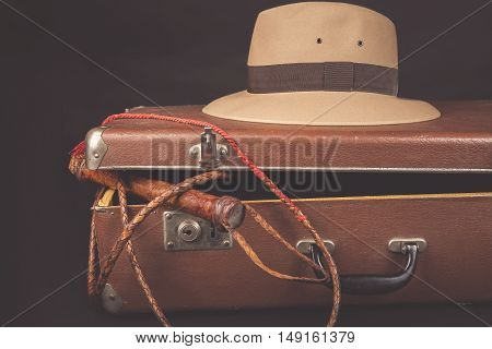 Travel and adventure concept. Vintage brown suitcase with fedora hat and bullwhip on dark background
