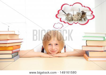 Smiling girl with many books dreaming about the cat