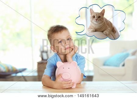 Little boy sitting at table with piggy bank and dreaming about the cat