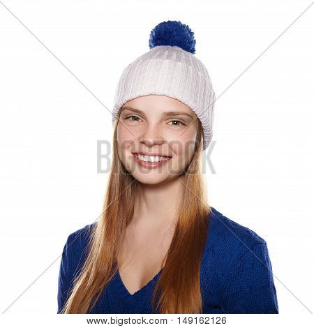 Portrait of attractive smiling girl in winter hat and sweater on a white background.