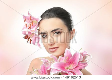 Beautiful young woman with flowers on color background. SPA concept.