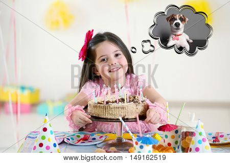 Happy little girl with tasty cake at birthday party dreaming about the dog