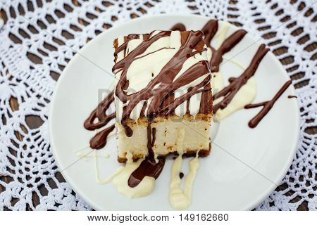 A square slice of cheesecake with dark and milk chocolate sauce