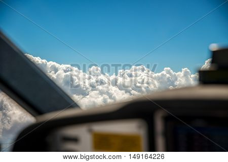 The cockpit of a small aircraft flying at seven thousand feet with the selective focus on the alto cumulus clouds outside the front window.