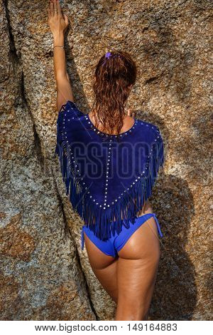 Attractive woman in summer clothes on brown rock background
