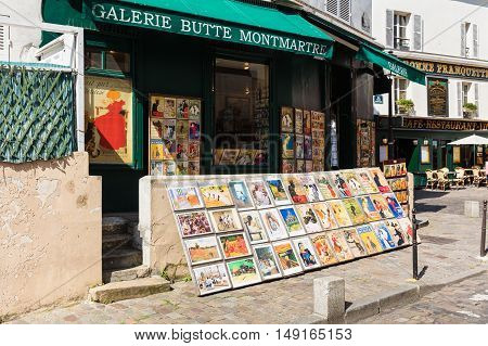 Paris France - July 06 2016: The charming quarter of Montmartre hill with traditional french cafes and art galleries. Old art prints for sale in Montmartre gallery.