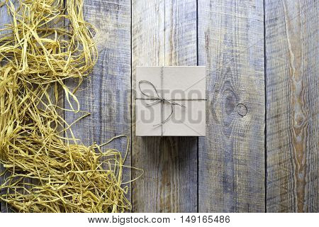 craft gift box on wooden table with natural raffia or twine close up