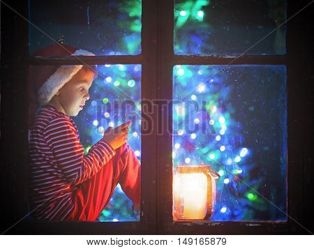 Cute Boy, Sitting On A Window Shield, Playing On Mobile Phone At Night, Christmas Time