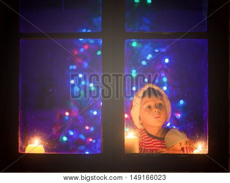 Cute Little Boy, Sitting On A Window At Night, Looking Outdoors, Waiting For Santa Claus And Christm