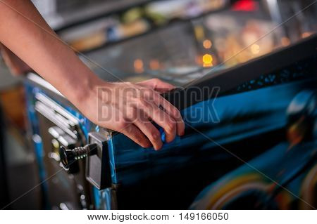 Hand of female pressing button and playing pinball machine
