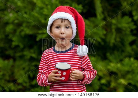 Sweet Boy In Striped Shirt With Santa Hat, Holding Cup With Tea Outdoors, Wintertime
