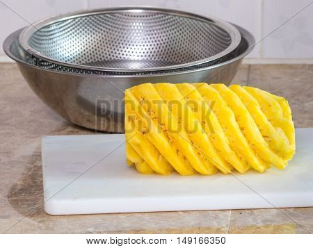 ripe pineapple on plastic white block or board with stainless steel bowl