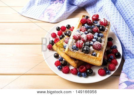 Soft waffle with blueberry and raspberry on blue linen napkin. Breakfast soft waffles with fresh berries