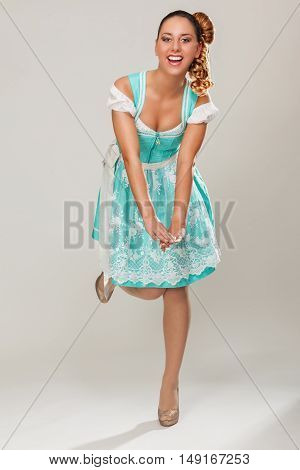 Young woman in dirndl smiling at the camera standing on one leg and showing her little Cleavage