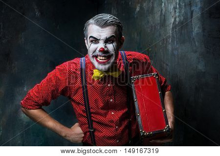Terrible clown and Halloween theme: Crazy red clown with suitcase on a dark background