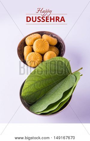 greeting card saying happy vijayadashmi or happy dussehra, indian festival dussehra, showing apta leaf or Bauhinia racemosa with traditional indian sweets pedha in silver bowl