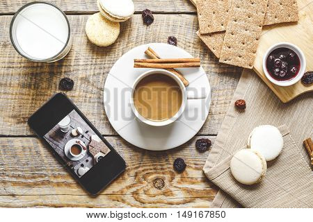 breakfast at home on wooden table with cup of milk coffee, croissants, macaroon and a smartphone