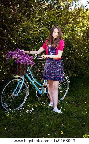 Beautiful Teenage Girl Standing Beside A Bicycle With A Basket Of Flowers