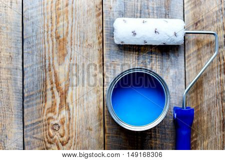 painting at home with open can of blue paint and brush on wooden background top view