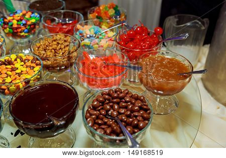 Assorted chocolate candy in a glass Candies in glass jars in candy shop