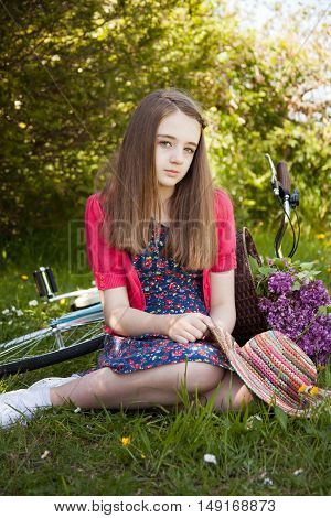 Beautiful Teenage Girl Sitting In A Field With A Bicycle With A Basket Of Flowers In Background