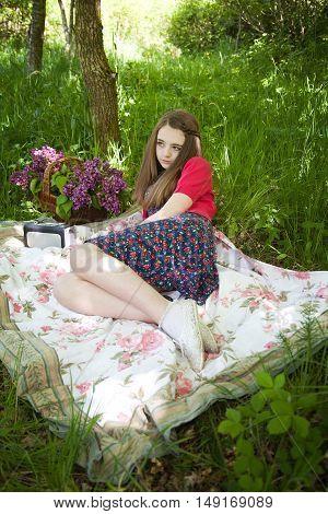 Beautiful Teenage Girl Sitting On A Blanket In Woodland