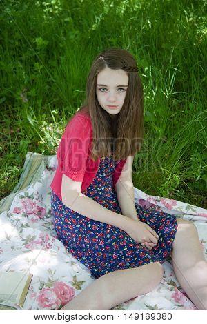 Beautiful Teenage Girl Sitting On A Blanket In A Meadow