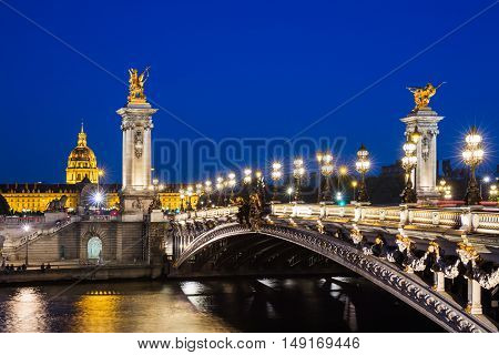 Pont Alexandre III bridge over river Seine and the Hotel des Invalides in the summer evening. Beautiful night illumination of bridge decorated with ornate Art Nouveau lamps and sculptures. Paris France