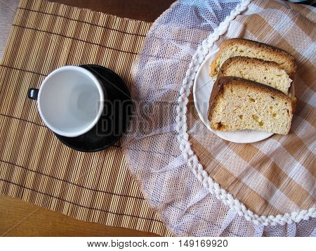 Piece of cake and black tea cup on the napkin on the table