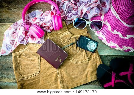 Travel accessories headphones camera glasses scarves skirts shoes hat in preparation for the trip.