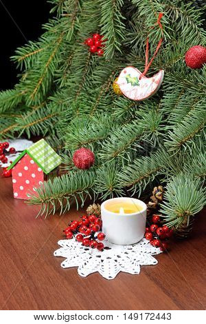 Little wooden bird is handmade and burning candle - holiday attributes. Branches of a Christmas tree decorated with baubles and red berries homemade wipes and a toy house cones. Festive atmosphere. New Year. Christmas. Family celebration.