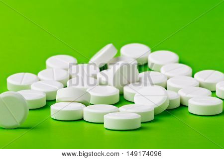 Heap of white round pills on green background
