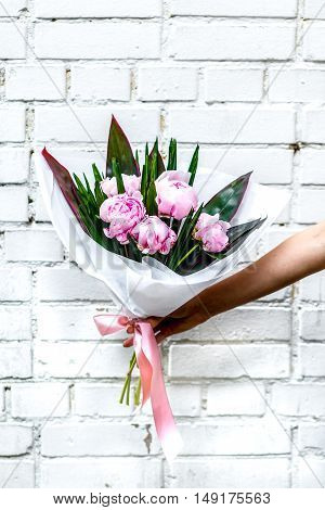 Bouquet of peonies in hand on white stone background against the wall - romantic gift