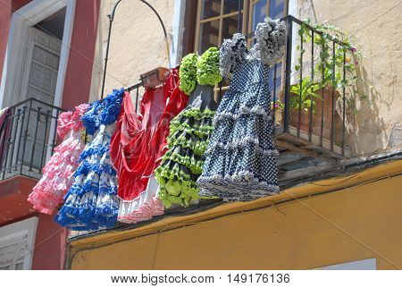 Five Spanish style dresses hanging from a balcony