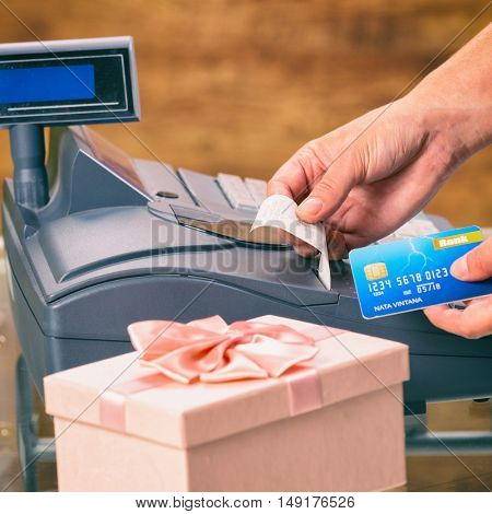Seller using cash register and holding credit card at giftshop