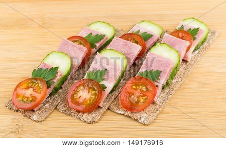 Three Crisp Bread With Bacon, Cucumbers And Tomatoes On Table