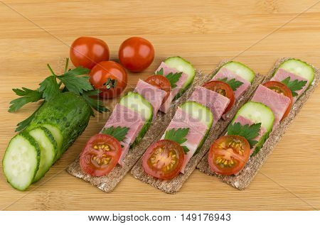 Crisp Bread With Bacon, Cucumbers And Tomatoes On Table