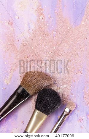 Makeup brushes on a light purple watercolor background, with traces of powder and blush on it. A vertical template for a makeup artist's business card or flyer design, with copyspace