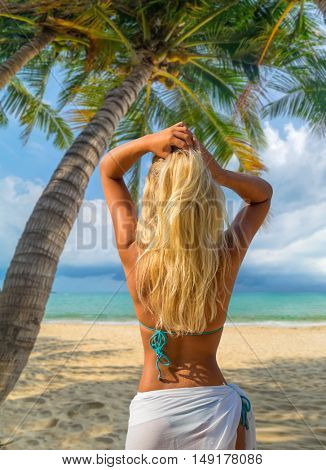 Beautiful blonde woman on the tropical beach under the palm tress