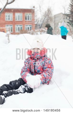 closeup portrait of Happy laughing girl in winter clothes outside playing in the snow drifts in the winter - Russia, Moscow - February 25, 2016
