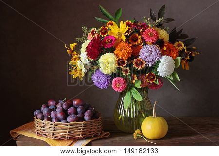 Still life with autumn bouquet of garden flowers in a vase pumpkin and plums in the basket.