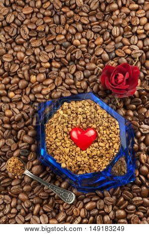 Coffee beans and instant coffee. Granules of instant coffee background. Instant coffee in a glass dish. Preparation of soluble coffee. Decorate store coffee.