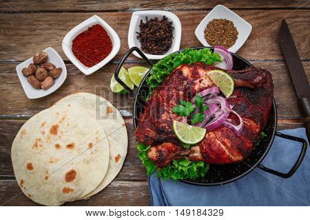 Indian tandoori leg chicken with spices and vegetables
