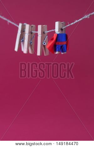 Powerful superhero character in blue suit red cape. clothespin leader and team concept photo. hangong on rope wooden clothespins. pink background. macro view