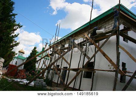 LUBESHIV UKRAINE - 13 JULY 2013 - Worker placing styrofoam sheet insulation to the wall