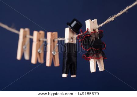 Macro view wooden clothespin characters on dark blue background. Bride in black red dress and groom character man suit hat. Love concept photo.