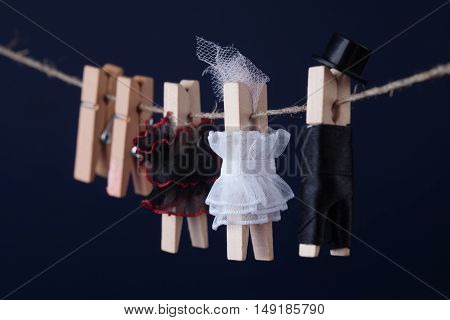 Clothespin characters on dark blue background. Woman in white black dresses, groom character man suit hat. Macro view, shallow depth of field
