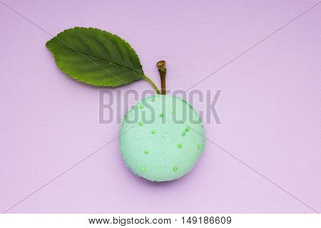 Creative concept photo of a macaroon with apple leaf and twig on purple background.
