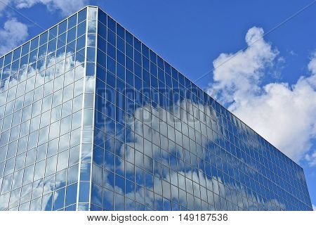 glass skyscraper with white fluffy clouds and blue sky reflection